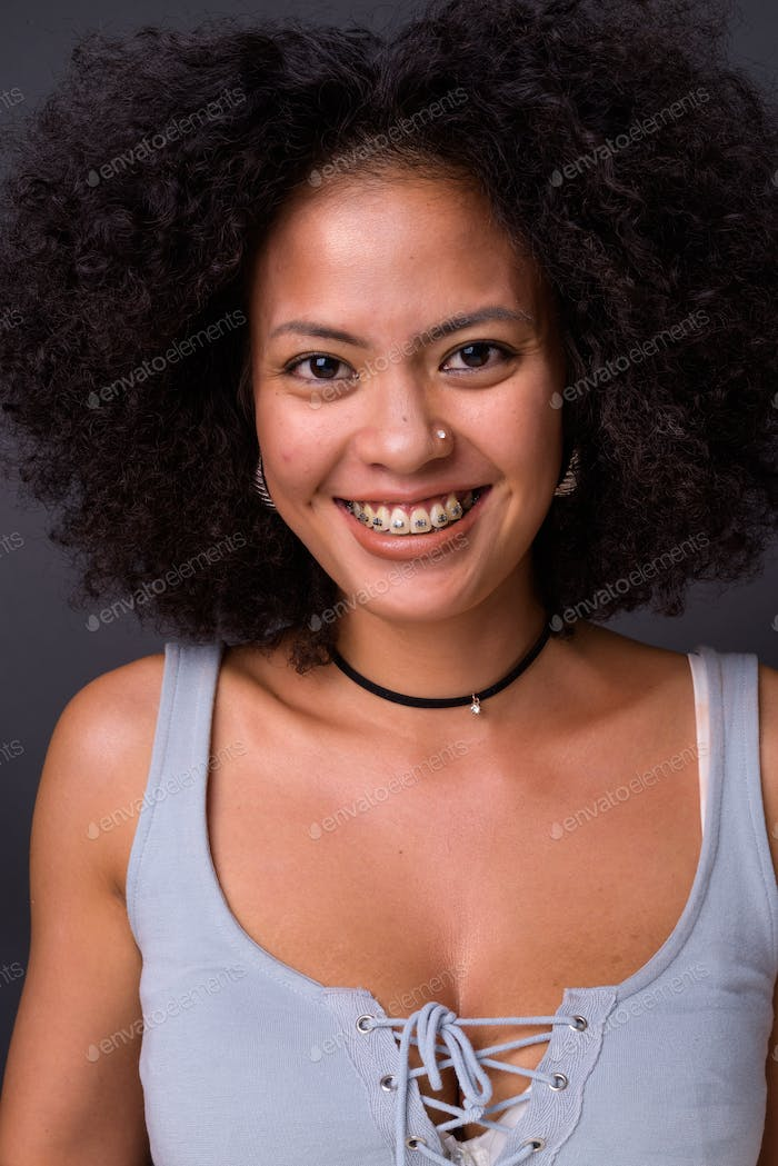 Young beautiful multi-ethnic African American woman against gray background