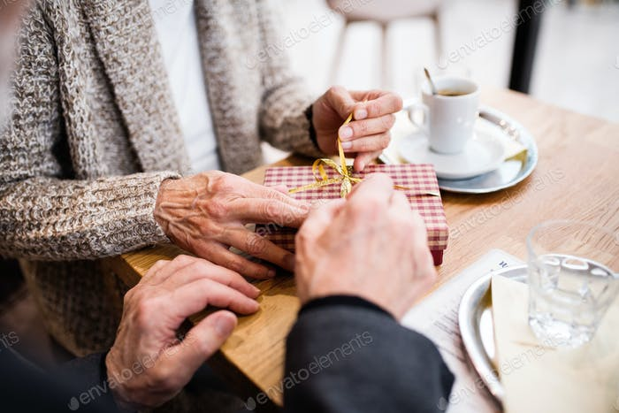 Senior couple with a present in a cafe. Christmas time.