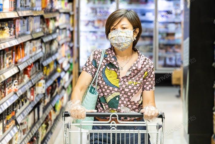 Asiatische Frau mit chirurgischer Gesichtsmaske und Handschuhen beim Einkaufen mit Einkaufswagen im Supermarkt