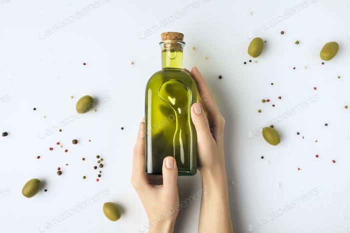 Cropped image of woman holding glass bottle of olive oil in hands isolated on white