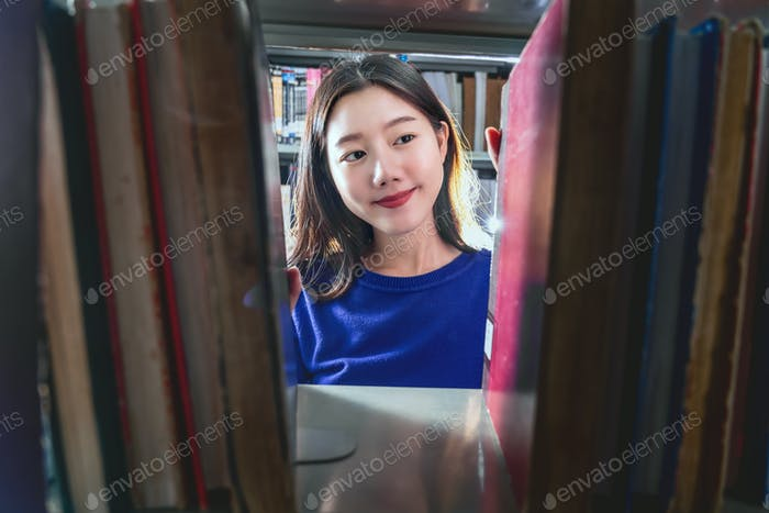 Asian young Student in casual suit searching the book in happiness feeling from book shelf