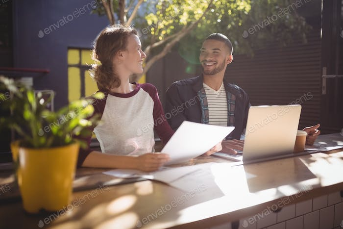 Smiling young creative professionals talking while sitting with laptop at coffee shop