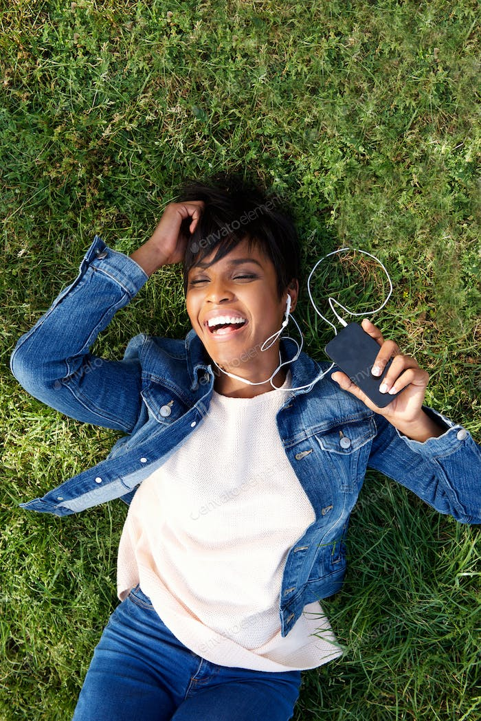 Laughing young african woman lying on grass with earphones and m
