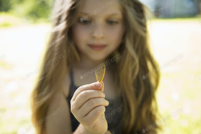 A girl holding a delicate lacey patterned discarded butterfly wing.