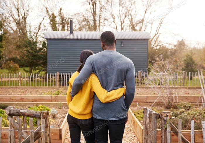 Rear View Of Couple Outdoors Spending Vacation In Eco Lodge
