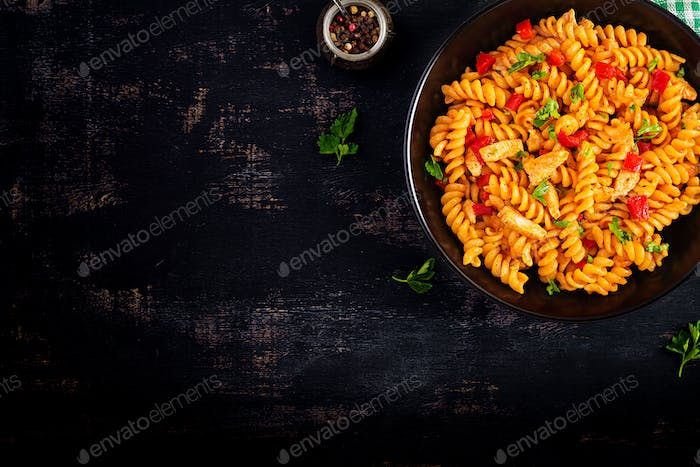 Fusilli pasta with chicken and sweet pepper in tomato sauce.