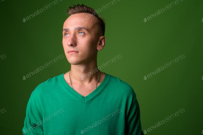 Studio shot of young handsome man against green background