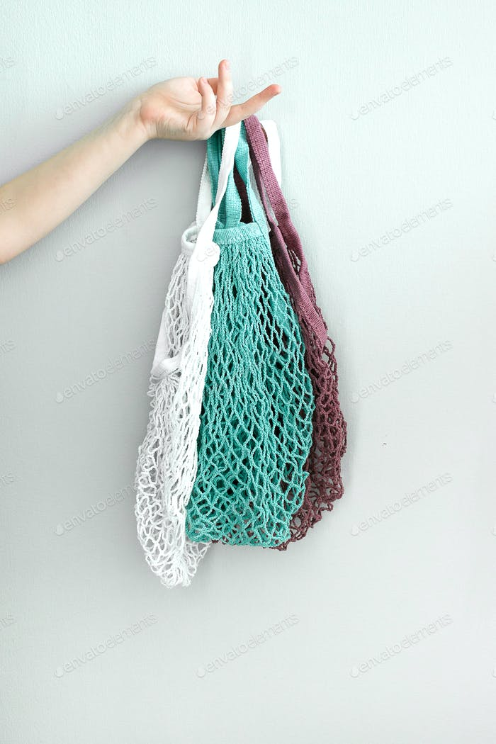 Reusable cotton bags, mesh bags in hand. Zero Waste, eco friendly concept.