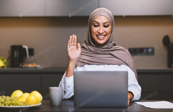 Muslim Lady At Laptop Making Video Call Sitting In Kitchen