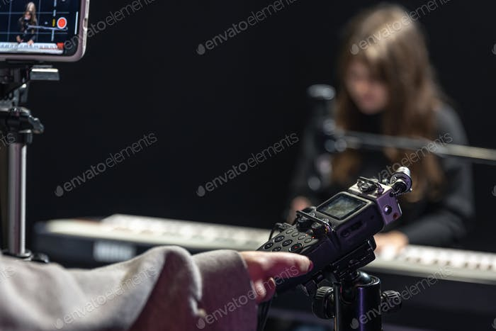Close-up of a recorder in the process of recording a piano playing.