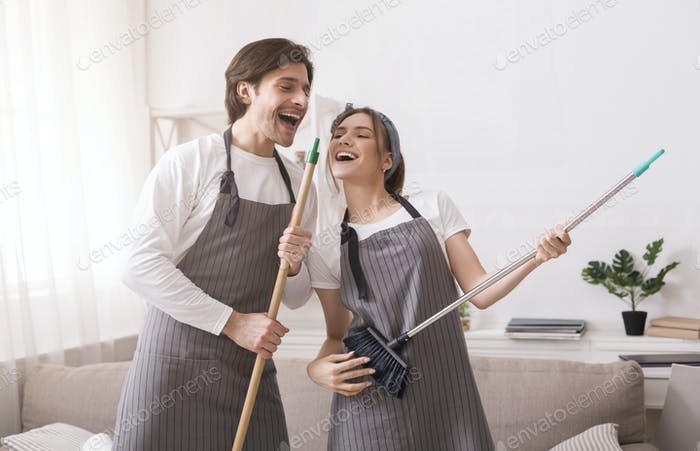 Couple having fun while tidying flat, playing on broom and mop