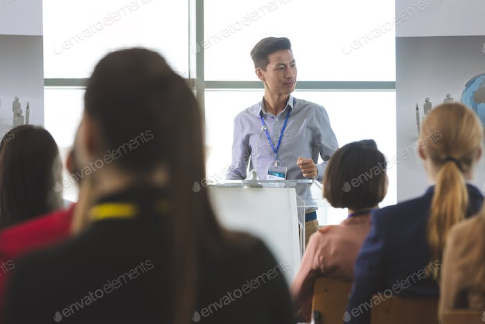 Businessman speaking at business seminar in front of business people sitting in office