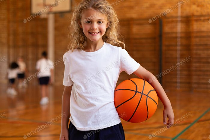 Happy schoolgirl holding a basketball and looking at the camera in a basketball court