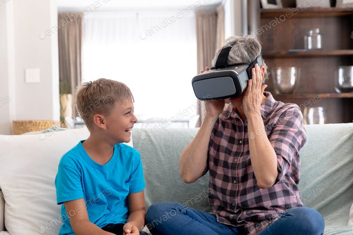 Senior Caucasian woman using a VR headset at home with his grandson