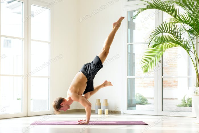 Muscular man doing Flying crow yoga pose