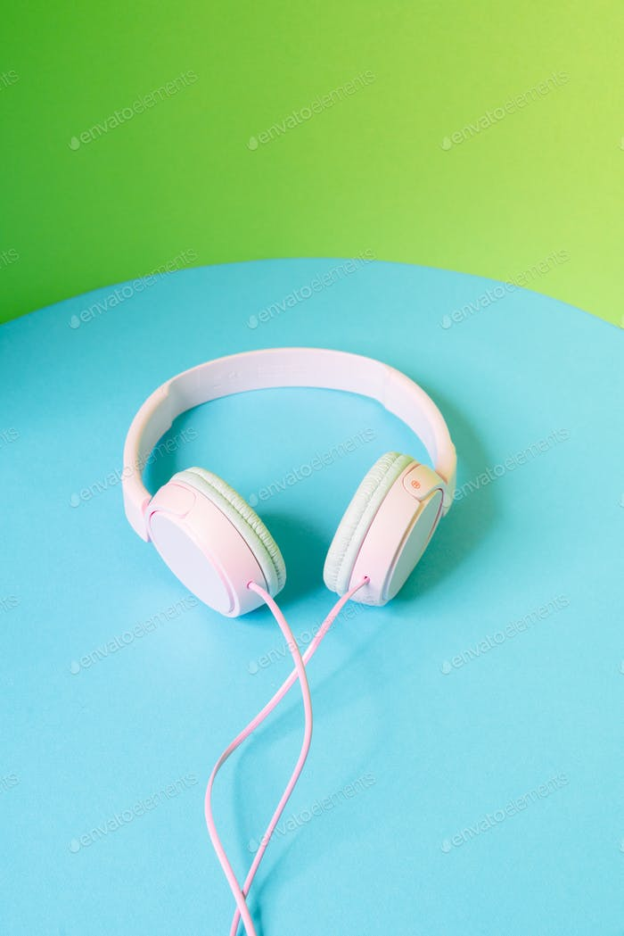 The front view of a pink wired headphones lying in the studio