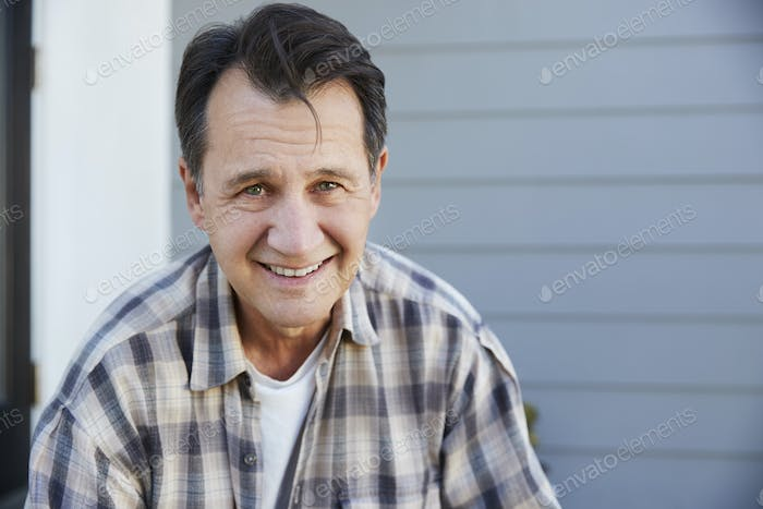 Portrait Of Senior Man Standing Outside Grey Clapboard House