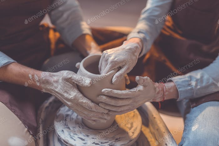 Human hands at the potter's wheel