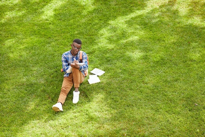 African Student Sitting on Grass