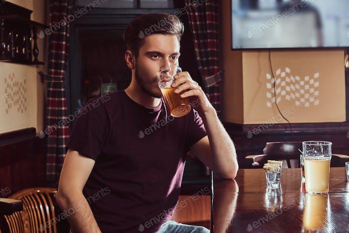 Junger glücklicher gutaussehender Kerl, der sich in der Bar oder im Pub ausruht, trinkt Bier an Holztheke.