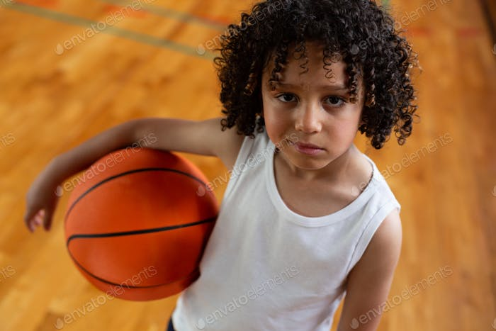 Schoolboy with basketball looking at camera in basketball court at school