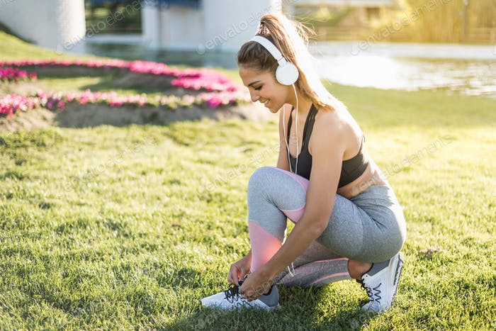 sports woman doing lawn exercises and stretching tying laces outdoor