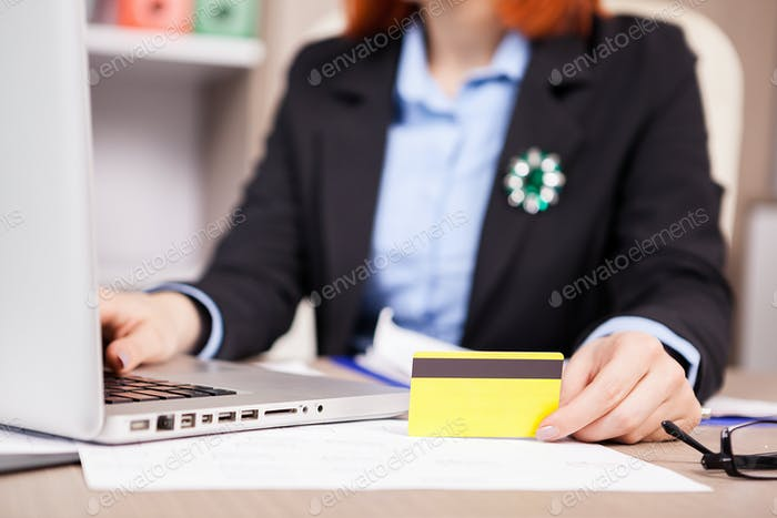 Businesswoman holding a credit card in hands