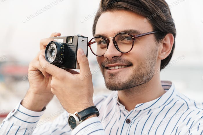 Photo of happy caucasian man taking photo on retro camera and smiling while walking on pier
