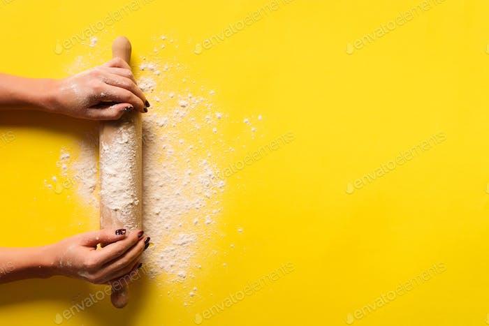 Mädchen Hände halten Nudelholz mit Mehl auf gelbem Hintergrund. Backmenü, Rezept, hausgemachtes Gebäck