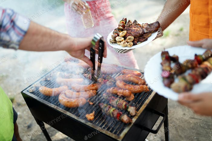 Selection of meat grilling over the coals on a portable barbecue
