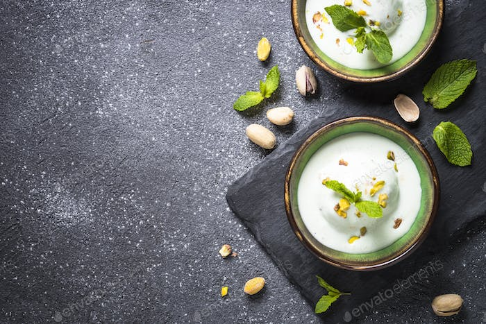 Pistachios ice cream in bowls on black stone table.
