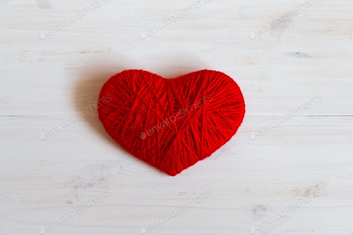 Red heart shape made from wool on white wooden background