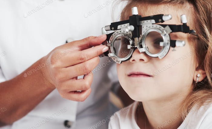 Close up photo. Doctor checking little girl sight and tuning the phoropter