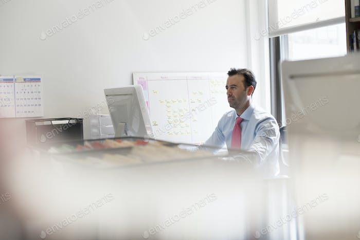 A man seated at an office desk using a computer. A wall chart with post it adhesive notes.