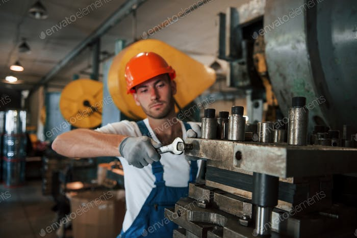 Heavy construction. Man in uniform works on the production. Industrial modern technology