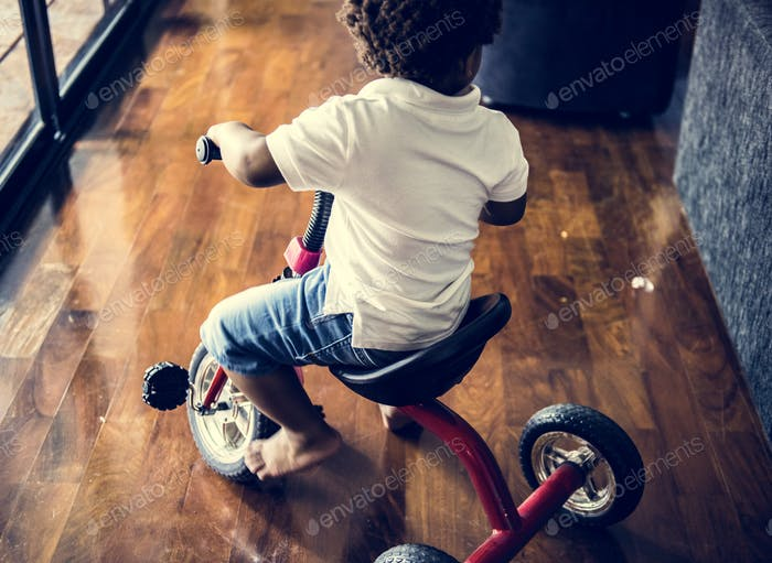 Black kid riding bicycle in the house