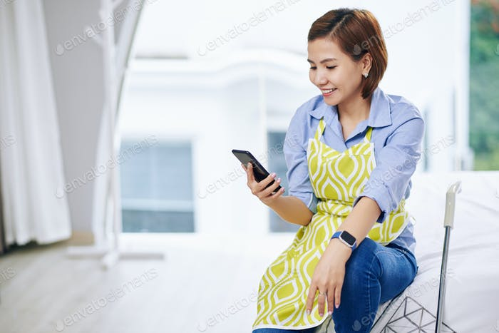 Hausfrau überprüfen Smartphone