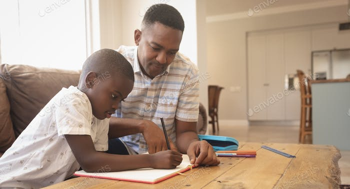 Side view of African American father helping his son with homework at table in a comfortable home