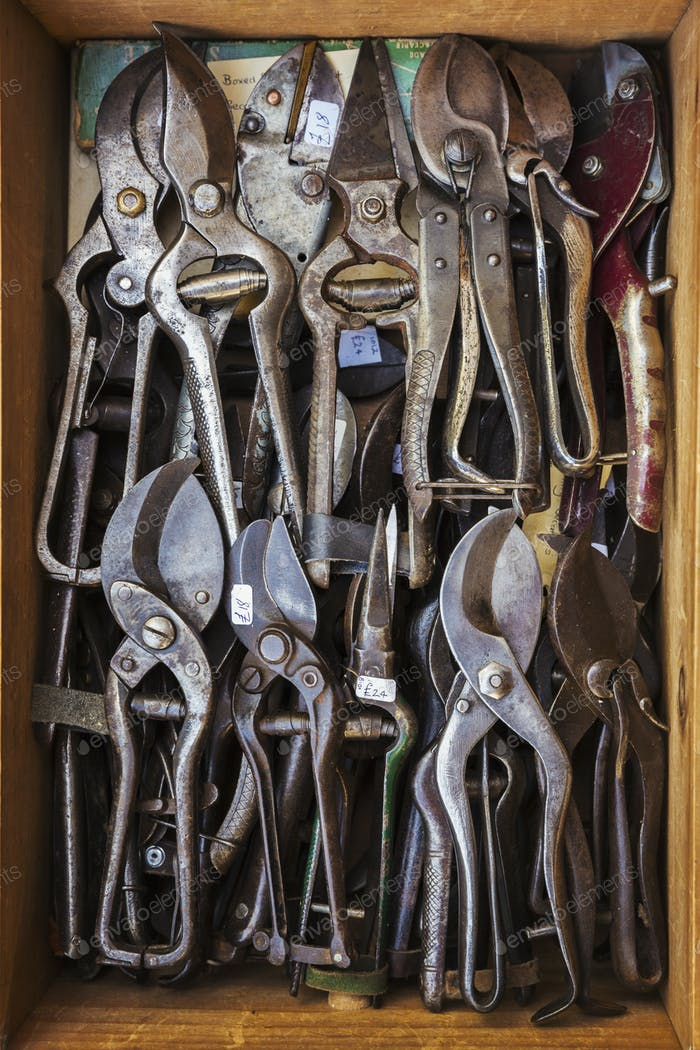 Overhead view of a box of old rusty worn metal shears, tin snips and pliers in a workshop.