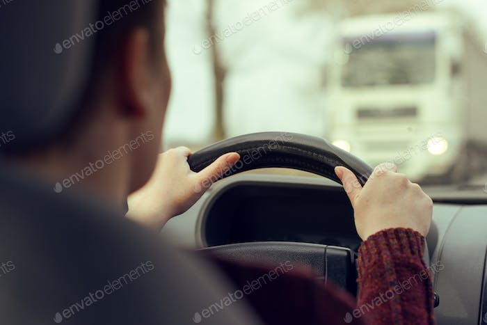 Woman driving car toward a large truck on the road