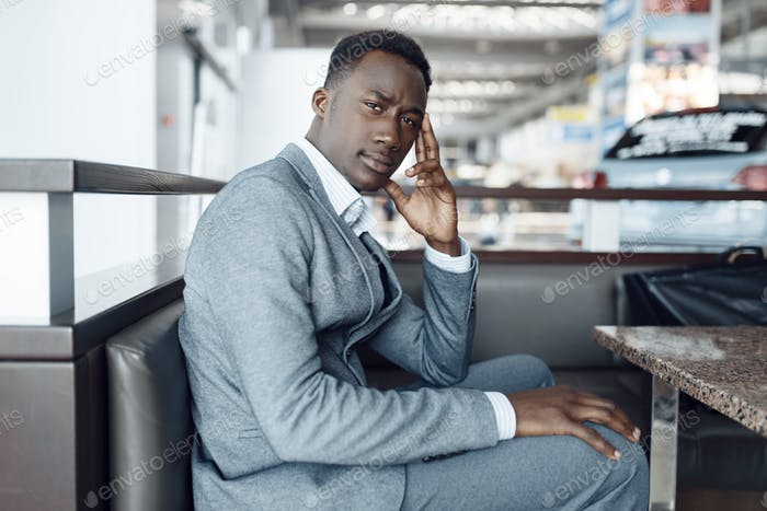 Black businessman sitting in car showroom