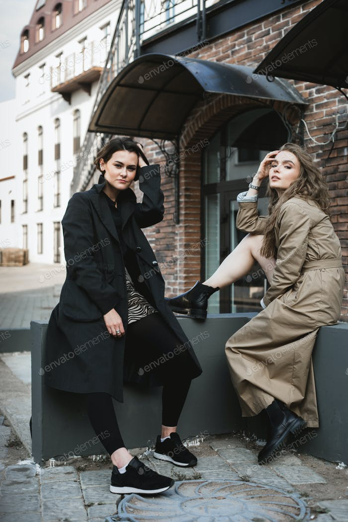 two pretty girls sitting together in the city