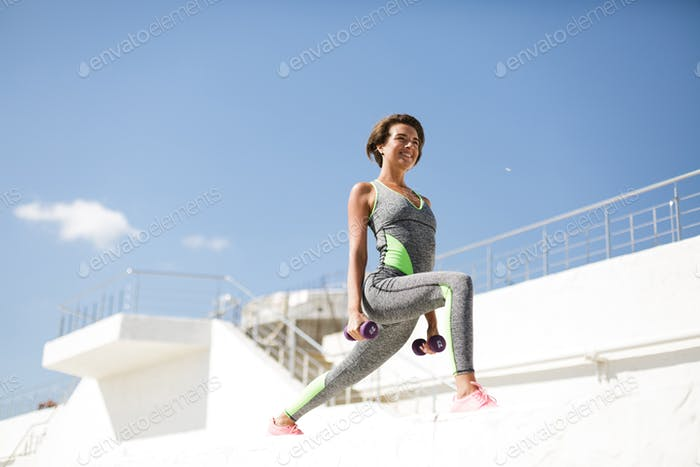 Beautiful smiling woman in modern gray sport suit and pink sneakers doing exercise with dumbbells