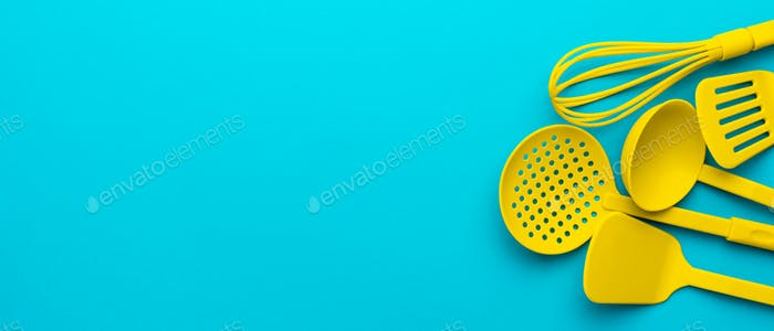 Yellow Plastic Kitchen Utensils Over Turquoise Blue Background With Copy Space