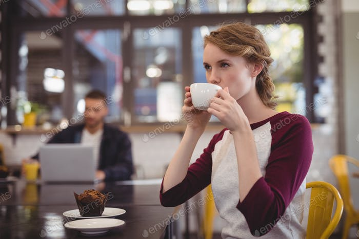 Beautiful young woman drinking coffee from cup at cafe