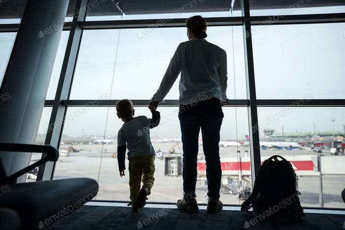 Mother and son standing near window in airport and watching landing field