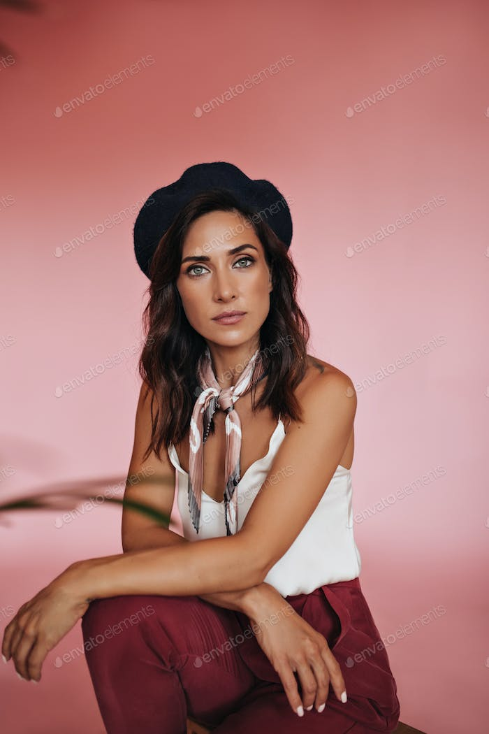 Lady in white top and silk scarf looks into camera on pink background. Green-eyed woman with short
