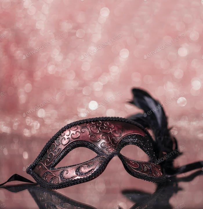 Karnevalsmaske mit Federn auf rosa Bokeh-Hintergrund.