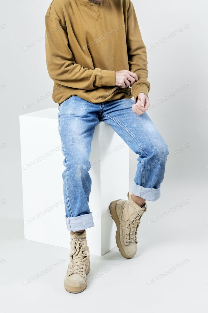 Man in brown sweater and blue jeans