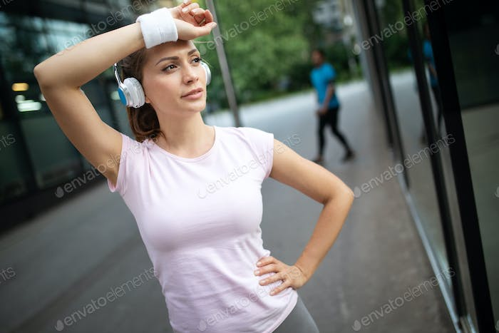 Tired runner woman sweating after running outdoor